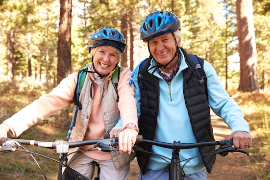 Senior couple on mountain bikes in a forest, portrait