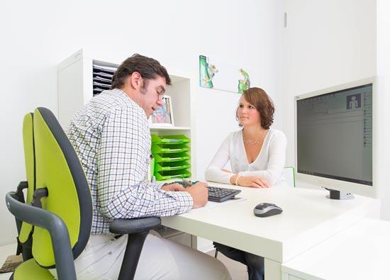 Dr-Tosch-im-Beratungsgespraech-mit-Patientin-am-Schreibtisch