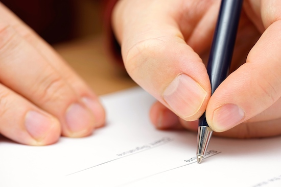closeup of businessman hand to sign  legal  or financial document