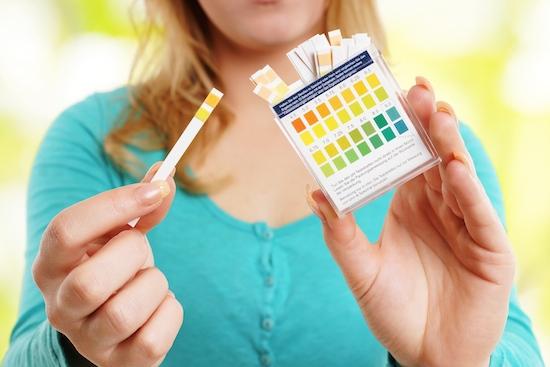 Frau testet PH-Wert mit Teststreifen