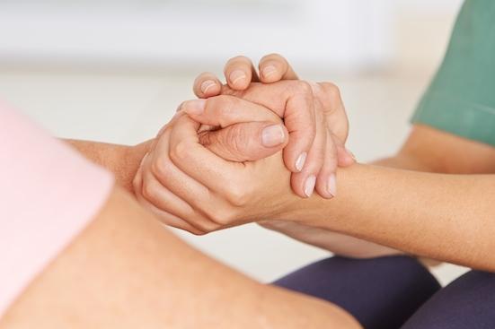 Krankenschwester hält die Hände einer Senorin zum Trost und zur Unterstützung