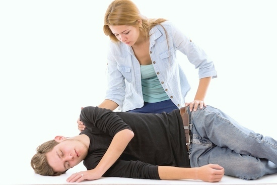 Couple demonstrating first aid techniques with male patient lying in recovery position and female sitting above him