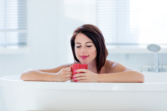 photo of the beautiful young woman having a bath and holding a drink